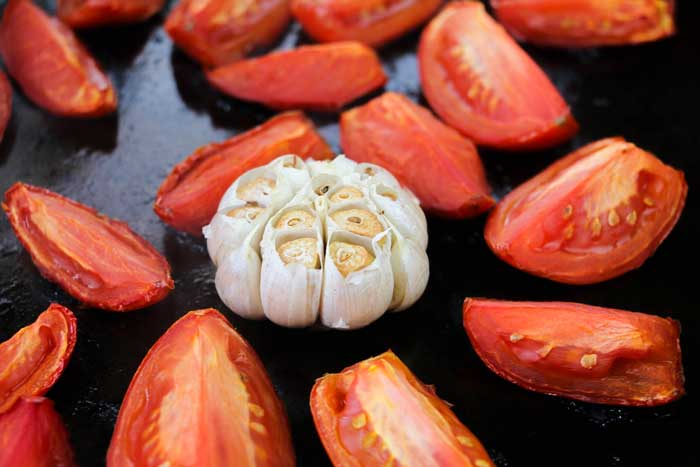 baking tray with roasted plum tomatoes and bulb of garlic on