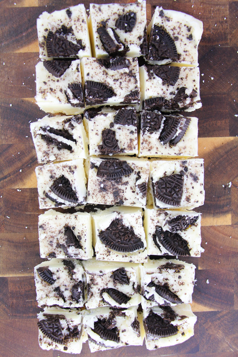 cutting up pieces of oreo fudge on a wooden chopping board