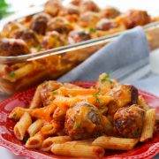 pasta bake with homemade meatballs on a red plate with the casserole dish behind a great family meal dea