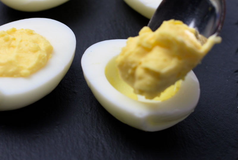 putting eggs mix back into eggs for deviled eggs