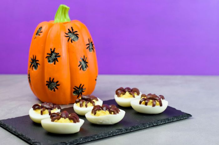 spooky Halloween appetizer spidered deviled eggs on a slate tray with a pumpkin behind