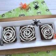 spider web brownies for halloween dessert easy to make with and for kids on a white tray with green halloween paper behind