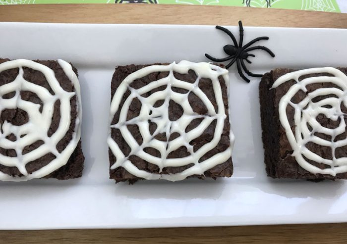 white plate with 3 chocolate brownies decorated with vanilla frosting spider webs for Halloween dessert
