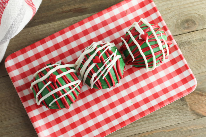 3 green hot chocolate bombs with red and white piping and a heart on each on a gingham plate with a wooden table behind for a grinch themed hot chocolate movie snack
