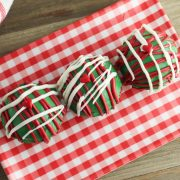 a red checked plate on a wooden table with 3 diy hot chocolate bombs made with green candy melts and decorated with red and white chocolate piped on and a heart on top for some grinch themed movie fun