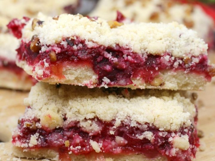 stack of cranberry filled cake bars with a crumble top on a wooden chopping board with pecan pieces around them