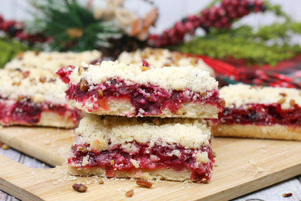 Cranberry cake bars on a wooden chopping board with Christmas foliage behind