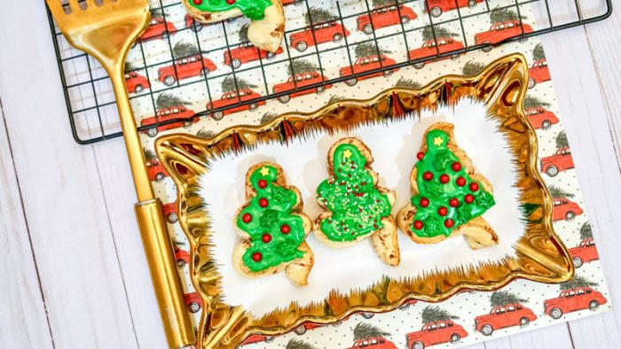 christmas tree shaped cinnamon rolls with green frosting and sprinkles on a christmas tray