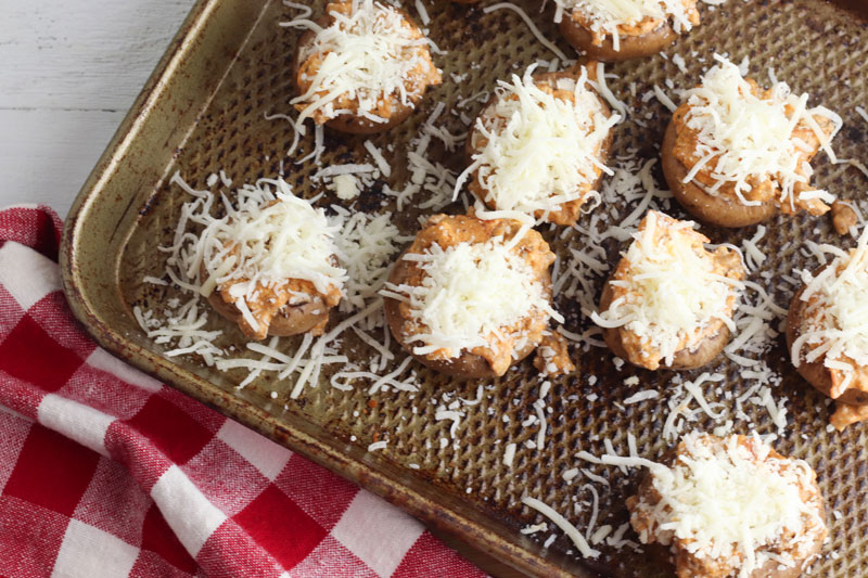 mozzarella cheese sprinkled on top of stuffed mushrooms for an easy appetizer