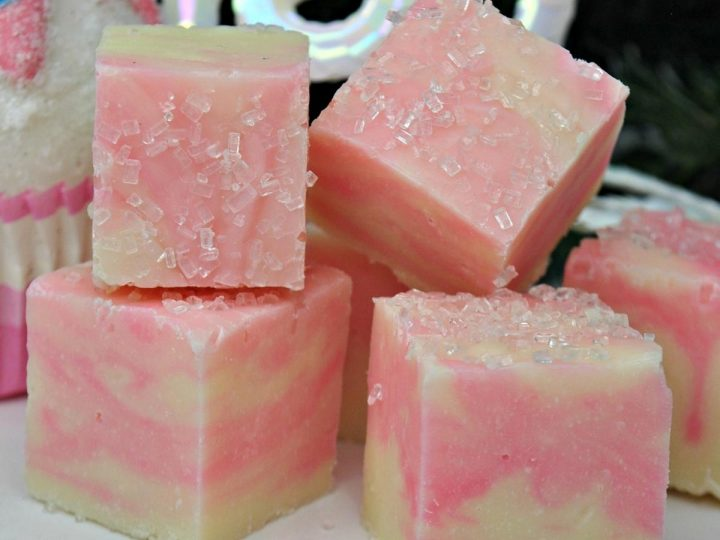 white and pink swirled chocolate and cotton candy fudge on in a pile with a black background behind