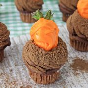 cute cupcakes with a orange candy coated strawberry for a carrot stuck in chocolate buttercream frosting with a sprinkle of chocolate cookie crumbs to look like a carrot patch ideal for easter parties and treats
