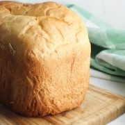 a loaf of white bread made in the bread machine on a wooden board with a green chequered tea towel behind