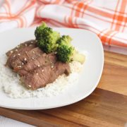 beef skirt strips with broccoli on top served on top of boiled white rice. All on a white plate on top of a wooden chopping board with a tea towel behind