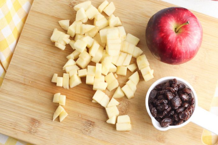 chopped apple and raisin ready to go into the bread machine on a wooden chopping board