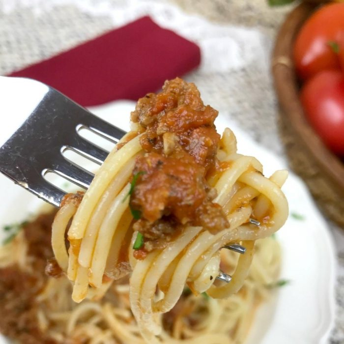 pasta sauce on a fork with spaghetti above a plate with tomatoes in the top right corner just peaking through