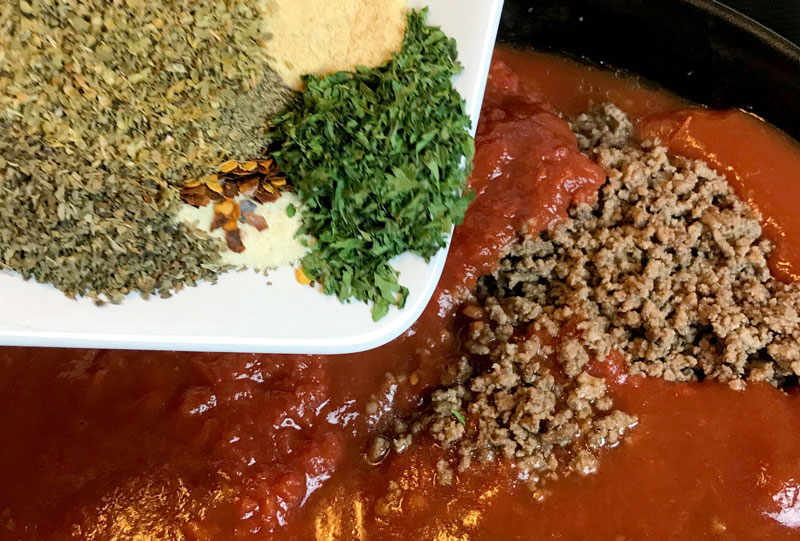 adding herbs and spices as to season a meat pasta sauce