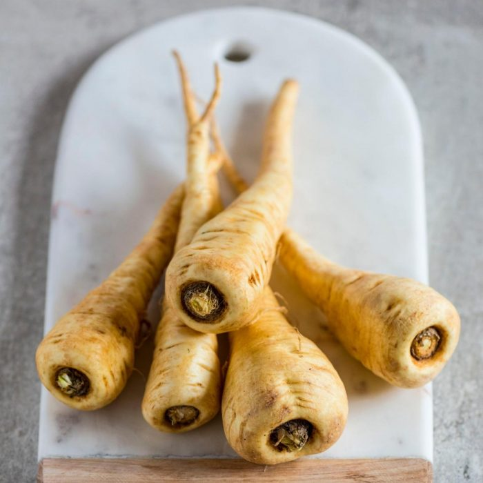 parsnips on a chopping board ready to be peeled and chopped for some delicious parsnip recipes for family dinner