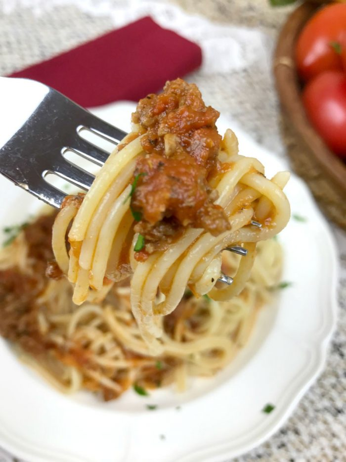 spaghetti on a fork with a scoop of homemade pasta meat sauce above a plate with spag bol
