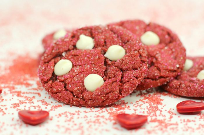 photo of a pile of red velvet cookies with white chocolates added on a white table with hearts and more sprinkles