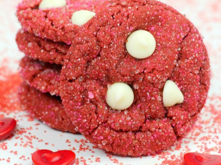 stack of homemade cake box red velvet crinkle cookies sprinkles with white chocolate chips on a background with hearts and cake sprinkles