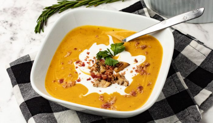 roasted butternut squash soup in a bowl with chicken and bacon bites swirled with coconut creame