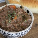 rustic beef stew with carrots, potatoes, celery and onions in a bowl with a loaf of homemade bread on a wooden chopping board