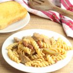 creamy sausage and bean pasta on a plate with a wooden spatula, tea towel and plate with a slice of garlic bread on top of a wooden table with a fork beside