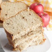slices of apple cinnamon and raisin bread on a plate fresh from the bread machine with 2 apples behind