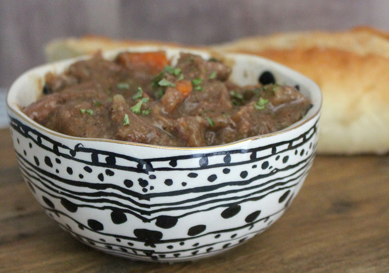 beef stew in a white bowl with black decor on a wooden board with a loaf of homemade bread in the background