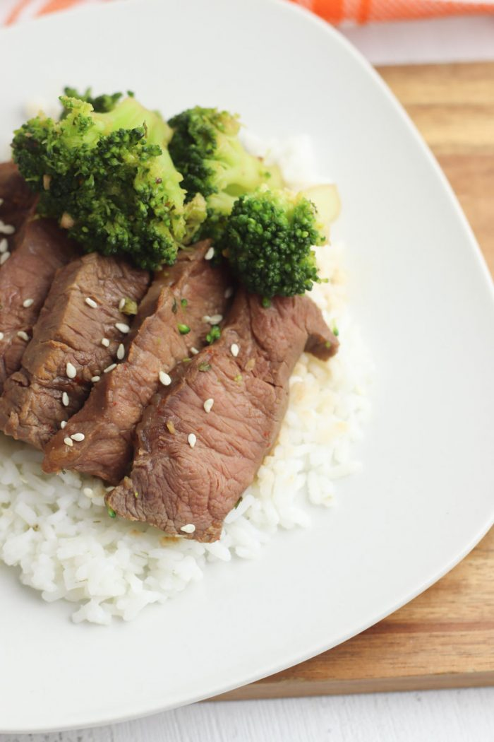 beef strips with broccoli on top served over white boiled rice on a white plate laid on a chopping board