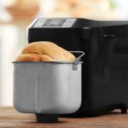 black bread machine with it's pan in front on a wooden worktop inside the pan is a white loaf that has been cooked in the machine