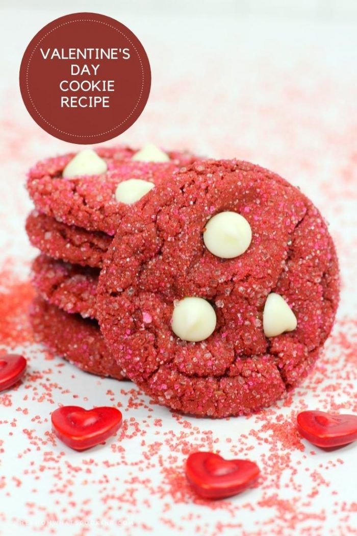 stack of valentine's day cookies made with red velvet cake mix and with white chocolate chips on top. In the picture they are stacked with a set of hearts sprinkled infront
