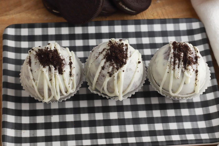3 cookie and cream hot cocoa bombs on a black and white checked serving tray with oreo cookies just seen in the background