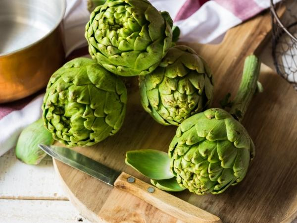 4 artichokes on a wooden chopping board in the kitchen with a knife beside ready to cook with
