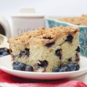 slice of blueberry crumble cake on a white plate with fresh blueberries around it. In front there is a red cloth and behind a colour cake pan as well as a sugar container