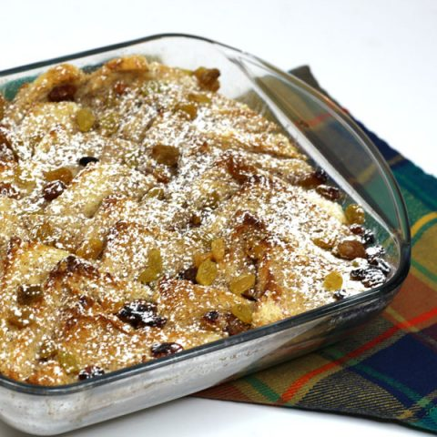 bread and butter pudding in baking dish with a sprinkle of powdered sugar in the top sitting on top of a tartan napkin on a white background