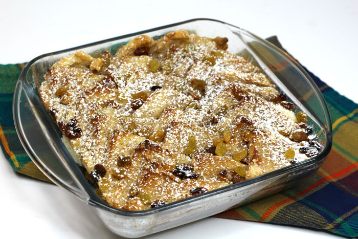 bread and butter pudding in a pyrex dish on a tartan napkin