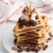 stack of carrot cake waffles with whipped cinnamon butter on top sprinkled with walnuts and raisins. someone from above is pouring maple syrup on top from a height. All on a white wooden table with a tea towel behind.