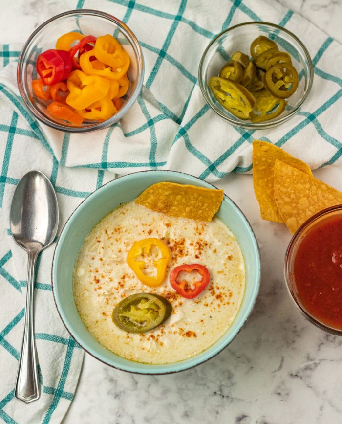 chicken enchillada soup with pepper rounds , tortilla chips and guacamole on a table