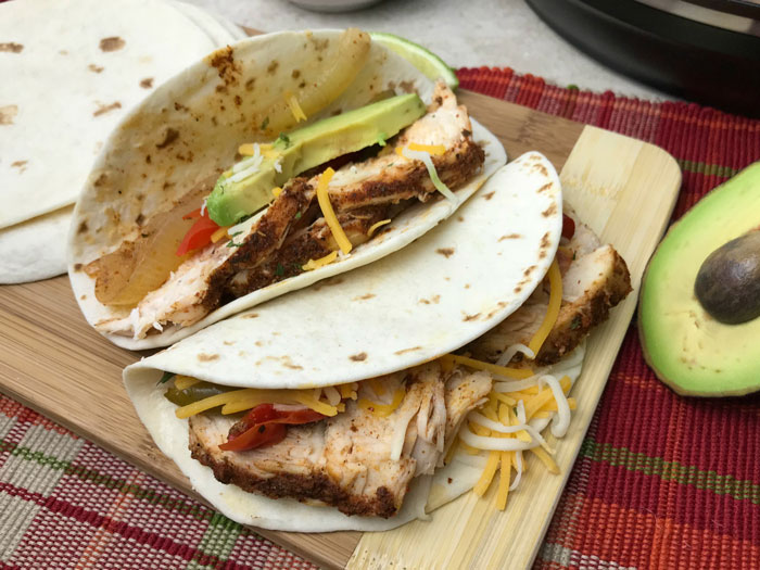 chicken fajitas with slices of avocado, shredded cheese on a wooden chopping board ready for the kids to eat