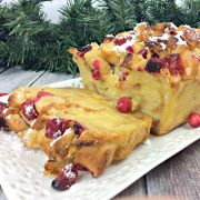 Bread and butter pudding on a plate made with eggnog custard and ripe fresh cranberries
