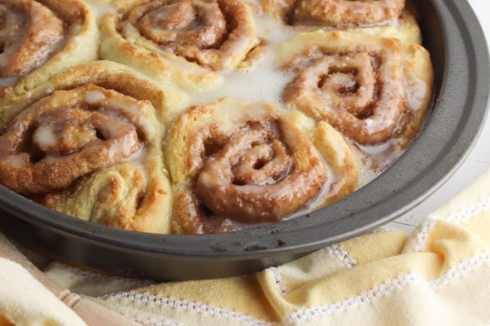 cinnamon rolls in a pan with sticky icing over the top