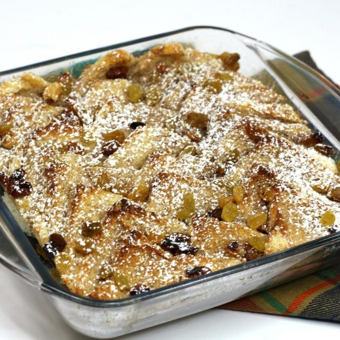 homemade bread and butter pudding with golden raisins sprinkled with icing sugar in a square pyrex dish on top of a tartan napkin on white background