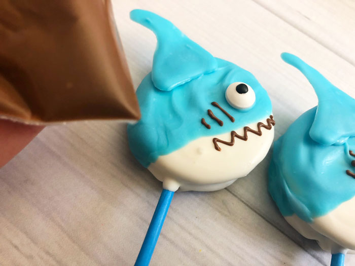 drawing on a gill and mouth with chocolate onto the shark oreo pops