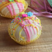 simple diy easter hot chocolate bomb with pink and yellow drizzled chocolate and spring flowers on top in a yellow cupcake case on a wooden table