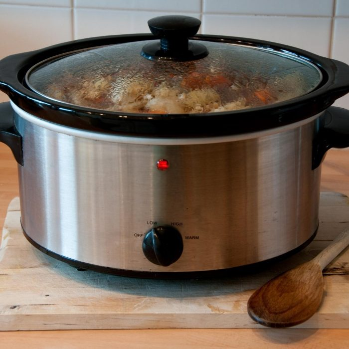 slow cooker filled with stew on a wooden chopping board in the family kitchen with a wooden spoon beside