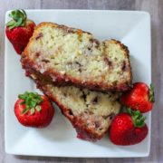 A white square plate with 2 slices of freshly baked strawberry pound cake with a homemade glaze and 4 ripe red strawberries around the outside