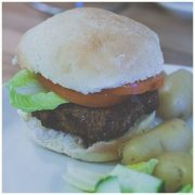 a homemade burger bun with burger lettuce and tomato on a plate with new potatoes and a salad