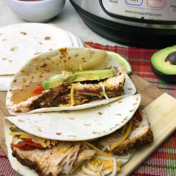 chicken fajitas on a wooden board with the instant pot behind slices of avocado and cheese are sprinkled inside the tortilla and a bowl can be seen in the distance with salsa in.