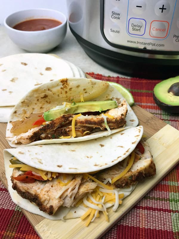 chicken fajitsa ready for dinner on a wooden chopping board behind is the instant pot that they were made in